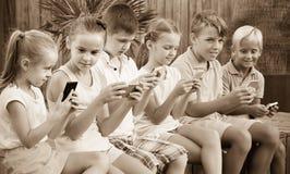 Niños en la edad de escuela que mira los teléfonos móviles y que sienta el outd Fotografía de archivo
