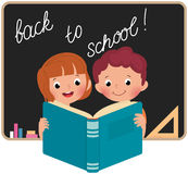 Niños en la escuela que leen un libro Imagenes de archivo