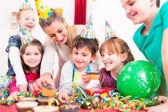 Niños en la fiesta de cumpleaños con los molletes y la torta Imagenes de archivo