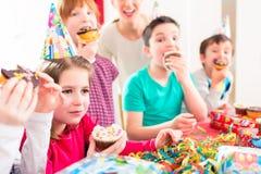 Niños en la fiesta de cumpleaños con los molletes y la torta Foto de archivo libre de regalías