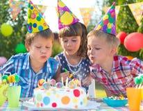 Niños en las velas que soplan de la fiesta de cumpleaños en la torta Imagenes de archivo