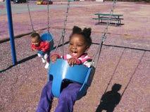 Niños en oscilaciones Imágenes de archivo libres de regalías