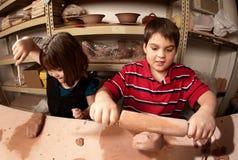 Niños en un estudio de la arcilla Fotos de archivo