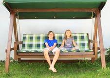 Niños en un oscilación del jardín Foto de archivo libre de regalías