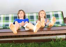 Niños en un oscilación del jardín Fotos de archivo libres de regalías
