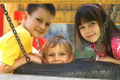 Niños en un oscilación del neumático Foto de archivo