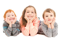 Niños felices con la cabeza en manos Imagen de archivo libre de regalías