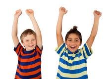 Niños felices con sus manos para arriba Imágenes de archivo libres de regalías