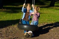 Niños felices en un oscilación del neumático. Fotografía de archivo