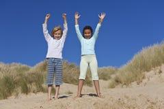Niños felices, muchacho y muchacha, jugando en la playa Imagenes de archivo