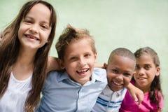 Niños felices que abrazan, sonriendo y divirtiéndose Foto de archivo