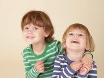 Niños felices que abrazan y que sonríen Imagen de archivo