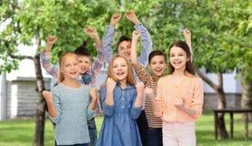 Niños felices que celebran la victoria sobre patio trasero Imagenes de archivo