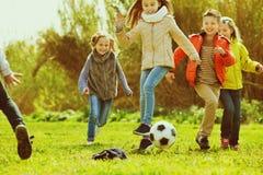 Niños felices que juegan a fútbol al aire libre Imagen de archivo
