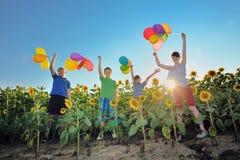 Niños felices que saltan en prado con los globos Imagenes de archivo