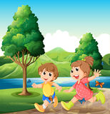 Niños felices y enérgicos que juegan cerca del río Imagenes de archivo