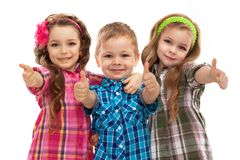 Niños lindos de la moda que muestran los pulgares para arriba Foto de archivo libre de regalías