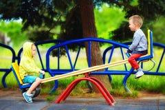 Niños lindos que se divierten en la oscilación en el patio Foto de archivo