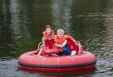 Niños lindos que tienen barcos de parachoques del montar a caballo de la diversión en un lago Imagen de archivo