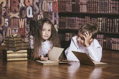 Niños muchacho y libros de lectura de los niños de la muchacha en biblioteca Imagen de archivo