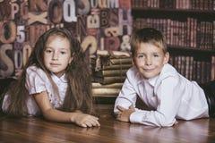 Niños muchacho y libros de lectura de los niños de la muchacha en biblioteca Imágenes de archivo libres de regalías