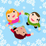 Niños multiculturales que juegan en la nieve que cae Imagen de archivo libre de regalías