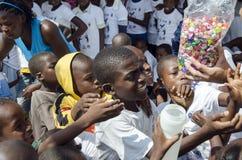Niños pobres que consiguen los caramelos Fotos de archivo libres de regalías