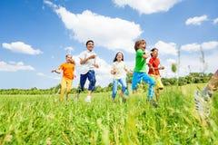 Niños positivos que juegan y que corren en el campo Imagen de archivo libre de regalías