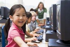 Niños que aprenden cómo utilizar los ordenadores. Foto de archivo