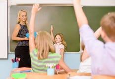 Niños que aumentan las manos que conocen la respuesta a la pregunta Fotos de archivo libres de regalías
