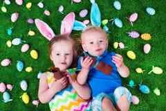 Niños que comen el conejo del chocolate en caza del huevo de Pascua Imagen de archivo libre de regalías