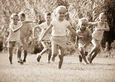 Niños que corren junto en parque Imagen de archivo