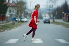 Niños que cruzan la calle en paso de peatones Foto de archivo libre de regalías
