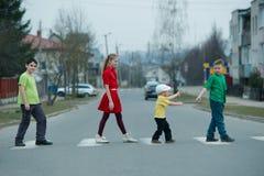 Niños que cruzan la calle en paso de peatones Imagen de archivo libre de regalías