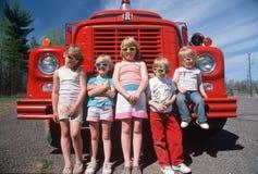 Niños que desgastan las gafas de sol con un coche de bomberos Imagen de archivo