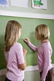 Niños que escriben en la pizarra en sala de clase Foto de archivo