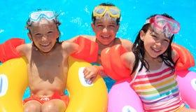Niños que flotan en piscina Foto de archivo libre de regalías