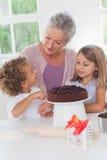 Niños que hacen la torta con la abuelita Foto de archivo