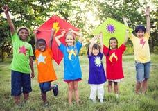 Niños que juegan al super héroe con las cometas Imágenes de archivo libres de regalías
