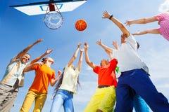 Niños que juegan a baloncesto con una bola para arriba en cielo Imagen de archivo
