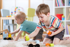 Niños que juegan con los juguetes en guardería o guardería u hogar Imagenes de archivo