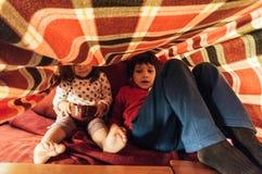 Niños que juegan debajo de una manta Imagen de archivo libre de regalías