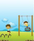 Niños que juegan el oscilación Foto de archivo libre de regalías