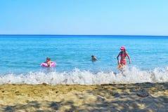 Niños que juegan en la isla Grecia de Sifnos de la playa Fotos de archivo