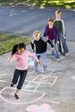 Niños que juegan hopscotch Fotos de archivo
