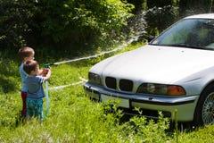 Niños que lavan el coche Imagen de archivo libre de regalías