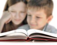 Niños que leen un libro Imágenes de archivo libres de regalías