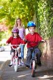 Niños que montan las bicis en su manera a la escuela con la madre Imagen de archivo