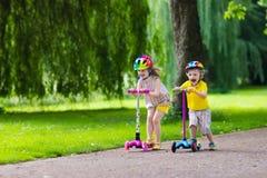 Niños que montan las vespas coloridas Fotos de archivo libres de regalías