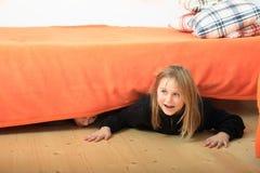 Niños que ocultan debajo de cama Imagenes de archivo
